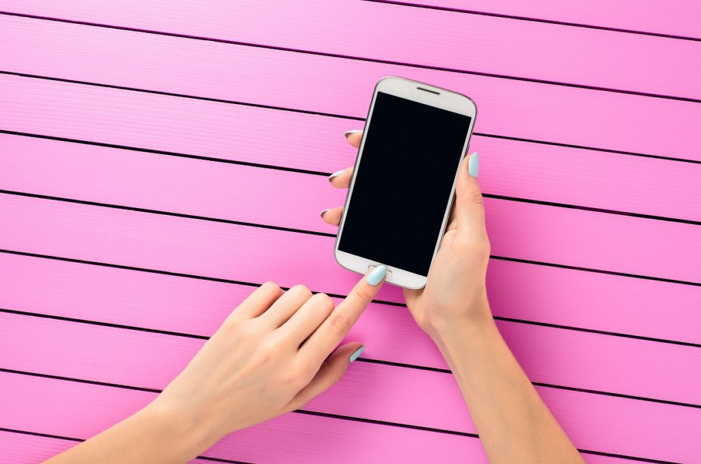 Female hand using white mobile phone over pink background